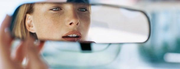 Frau trägt Lippenstift im Autospiegel auf und ist bereit fremdzuflirten