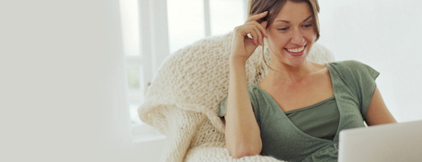 Frau erkundigt sich mit Laptop auf dem Schoß über die meistegestellten Fragen zu ElitePartner