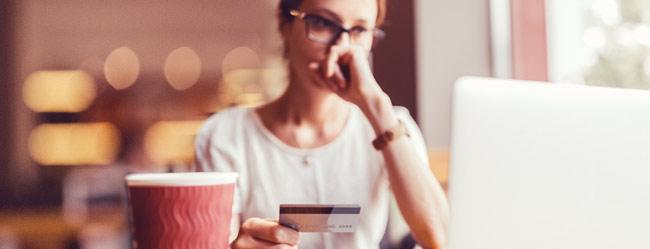 Frau sitzt unsicher vor Laptop mit Kreditkarte in der Hande symbolisch für den Schutz gegen Romance Scamming bei ElitePartner