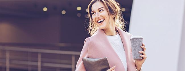 Frau läuft happy entlang der Straße, weil Sie den Test gemacht hat und herausgefunden hat wie hoch ihr Marktwert ist