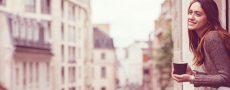 Singles in Deutschland: Frau lehnt sich aus Fenster und blickt zufrieden in die Ferne