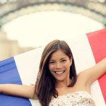 Grund einen Franzosen zu daten: Frau vor dem Eifelturm hält symbolisch dafür französische Flagge hoch