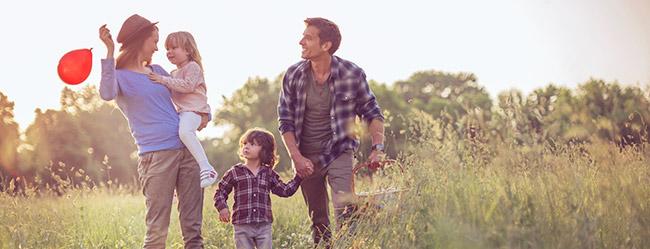 Verabredung mit Kind: Mann und Frau treffen sich mit zwei Kindern und machen Spaziergang durch die Natur