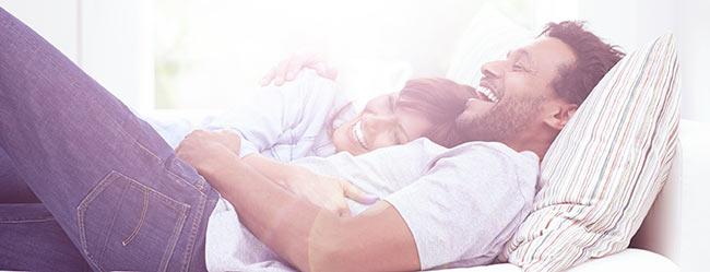 Frau liegt Mann im Bett im Arm und beide sind glücklich nach ihrer Partnersuche ab 40