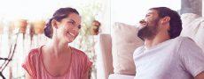 Mann und Frau in glücklicher Beziehung heute lachen sich glücklich im Wohnzimmer an