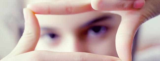 Wie sich Elite definiert zeigt Person die mit ihren Fingern ein Quadrat vor Ihrem Gesicht bildet und damit den Begriff eingrenzt.