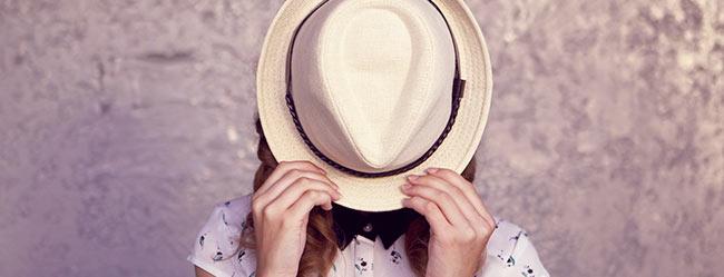 Symbolbid von Traumfrau durch Frau die ihr Aussehen hinter einem Hut versteckt