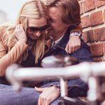 Mann flüstert seiner Frau ein Geheimnis aus ihrer Beziehung ins Ohr und hat sie dabei auf dem Schoß sitzen