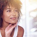 Frau schaut sich zufrieden im Spiegel an nachdem sie ihre Persönlichkeitsanalyse gelesen hat