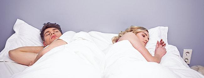 Mann und Frau liegen einander mit dem Rücken zugewandt im Bett weil sie eine kein Sex an Weihnachten haben