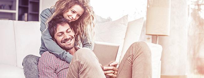 Freundin finden: Mann liegt glücklich mit Frau im Wohnzimmer mit Tablet in der Hand