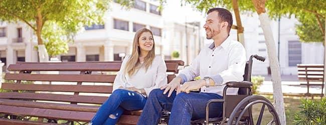 Mann im Rollstuhl geht die Partnersuche mit Handicap an und sitzt mit einer Frau im Park