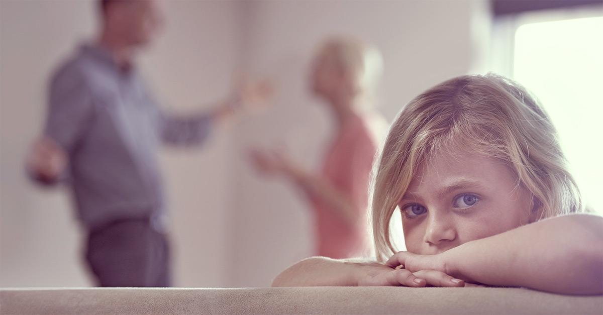Kind sitzt traurig am Tisch während Eltern im Hintergrund die Trennung mit Kind diskutieren