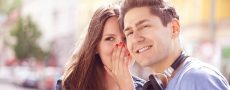 Frau flüstert Ihrem Partner Dinge ins Ohr, die er noch nicht wusste