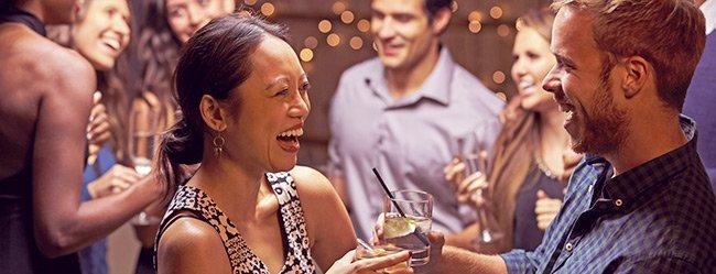 Mann und Frau lernen sich auf Party mit den richtigen Smalltalk Fragen kennen