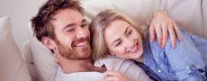 Mann und Frau kuscheln auf dem Sofa und genießen Ihre Zweisamkeit