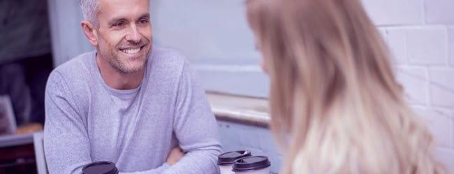 Mann mit Altersunterschied lächelt Frau an