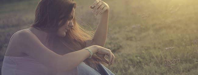 Frau sitzt draußen auf dem Rasen und hat eine Beziehungskrise