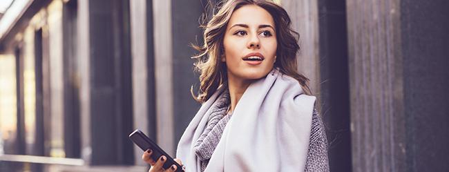 Frau beim Dating am Smartphone ist überrascht von den aktuellen Beziehungstrends