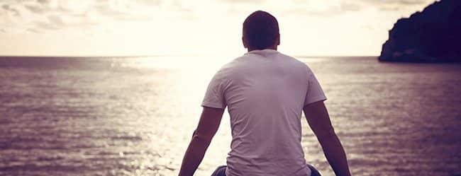 Mann sitzt allein am Meer und denkt über Beziehungsunfähigkeit nach