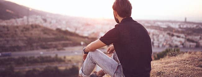 Mann sitzt draußen und denkt über Bindungsstörung nach