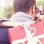 Date Geschenk: Frau umarmt Mann und hat Geschenk in der Hand