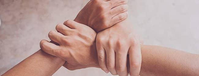 Drei Hände greifen ineinander als Symbol für Dreiecksbeziehung