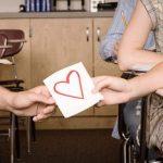 Symbolische Darstellung der ersten Liebe: männliche und weibliche Hand halten gemeinsam an Papier mit rotem Herz in Klassenzimmer