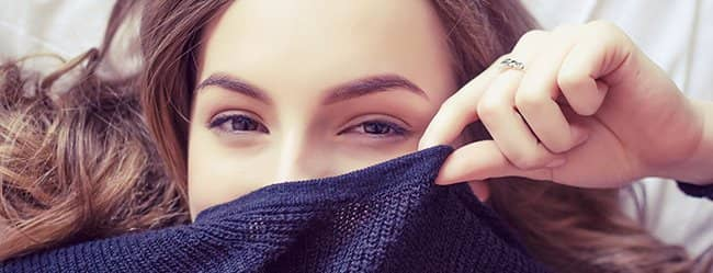 Frau zieht Pullover bis zur Nase und will Mann verführen