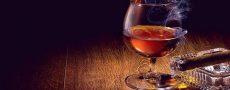 Glas Whisky und Zigarre auf dem Tisch als Symbol für Männlichkeit