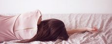 Ödipuskomplex der Frau bildhaft dargestellt durch Frau die mit dem Rücken zugewandt auf dem Bett liegt