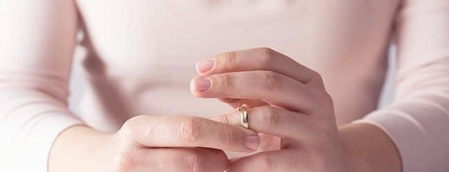 """Hände einer Frau, die mit Ring am Finger spielt und sich fragt: """"Warum heiraten?"""""""