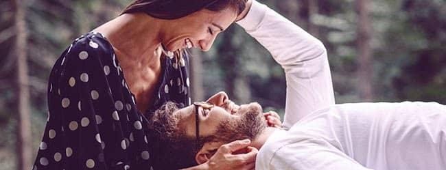 Was Frauen wollen: Frau ist über liegenden Mann gebeugt