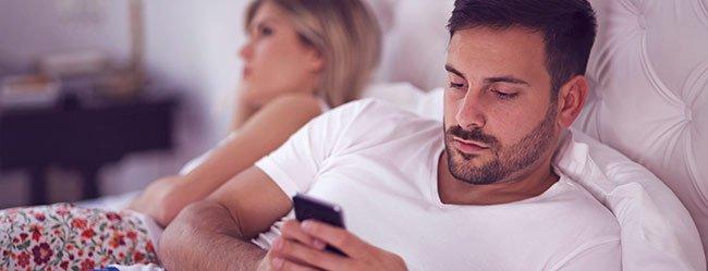 Smartphones belasten die Beziehung dargestellt durch ein Paar das im Bett jeweils vertieft ins Handy ist