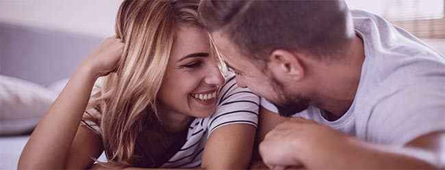 Mann und Frau in einer Rebound-Beziehung liegen auf dem Bauch und lächeln sich an.