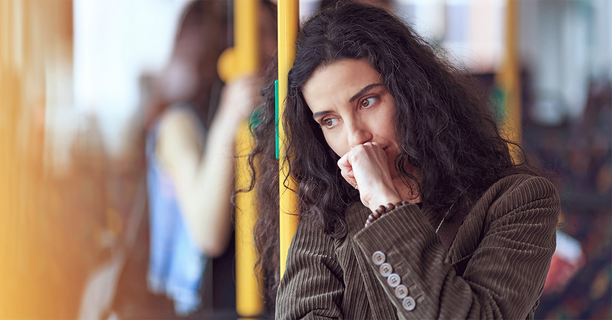 Frau steht in der Bahn und hat Schuldgefühle nach der Trennung