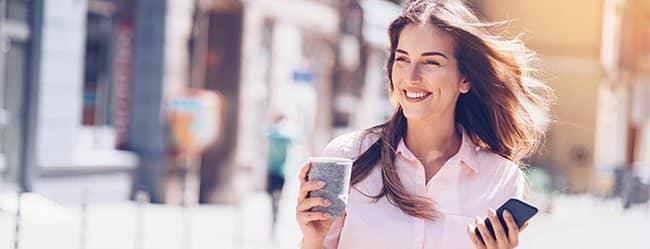 Verliebte Frau läuft mit rosaroter Brille durch die Stadt