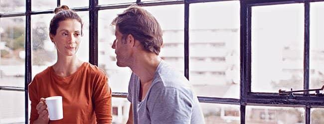 Frau und Mann sitzen am Fenster und führen ein klärendes Gespräch über ihre Beziehung