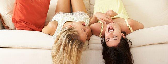 Frau genießt das Single Leben mit der besten Freundin beim Quatsch machen auf der Couch