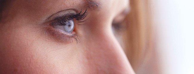 Frau guckt misstrauisch aus dem Fenster, da sie von Lügen in der Beziehung betroffen ist