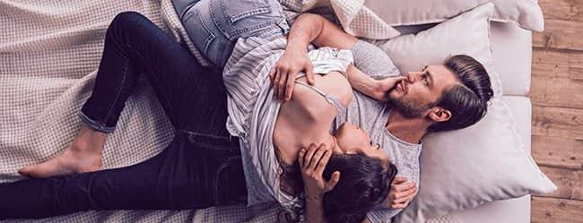 Paar liegt auf einem Bett, der Mann hat Angst vor der Liebe