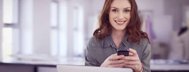 Frau am Handy informiert sich über ElitePartner-Kosten