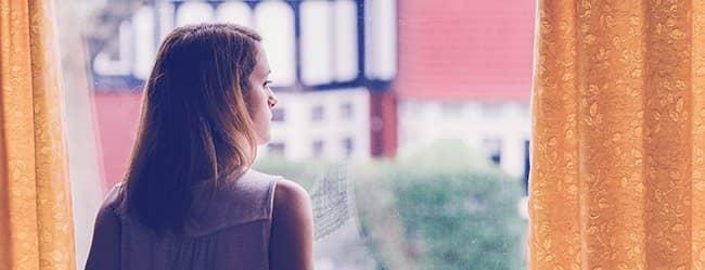 Frau schaut aus dem Fenster als Symbol für emotionale Abhängigkeit