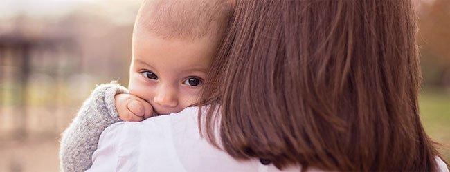 Frau zum Rücken zur Kamera hat Kind auf dem Arm das in Kamera schaut als Symbol für den Kinderwunsch in einer Beziehung