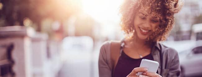 Frau am Handy ließt Online Dating Tipps