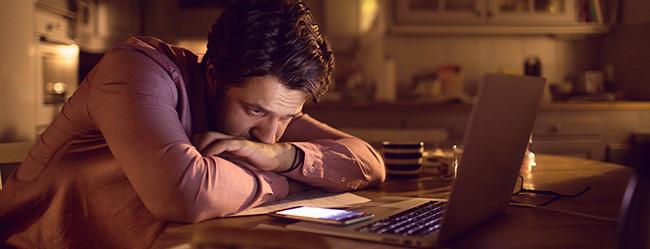 Mann fragt sich warum sie sich nicht mehr meldet und sitzt verzweifelt vor seinem Laptop