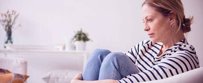 Frau sitzt mit herangezogenen Beinen auf der Couch. Sie versucht ihr Gefühlschaos in den Griff zu bekommen