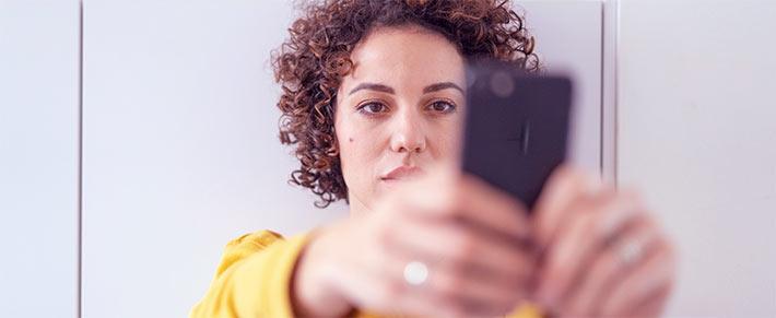 Frau ist schaut gefühlskalt auf ihr HandyFrau ist schaut gefühlskalt auf ihr Handy