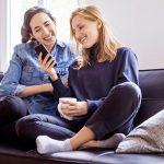 Zwei Frauen mit Handy unterhalten sich über Frauen anschreiben