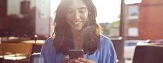 Frau probiert ElitePartner Eisbrecher am Handy aus